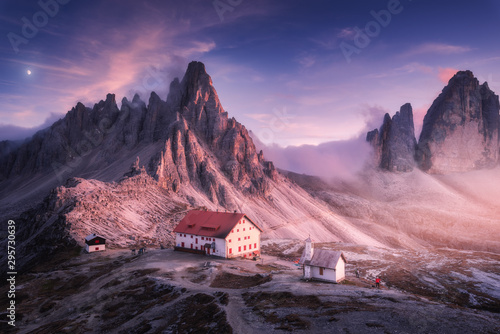 Obraz Mountains with beautiful house and church at sunset in autumn. Landscape with buildings, high rocks, purple sky with moon and clouds, sunlight. Mountains in fog. Tre Cime park in Dolomites, Italy - fototapety do salonu