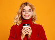 canvas print picture happy emotional cheerful girl laughing  with knitted autumn sweater and Cup of coffee on colored yellow background.