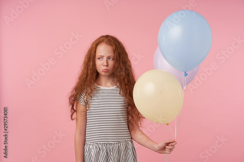 Studio photo of offended little girl with foxy curly hair posing over pink background with colored air ballons, looking aside sadly and folding lips, being in bad spirit, wearing striped dress
