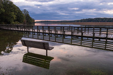 Flooded Dock And Park Bench At Sunrise On A Cloudy Morning On A Riverbank With Reflections