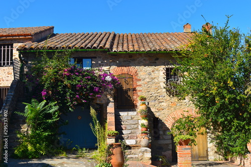 Foto auf Gartenposter Altes Gebaude Traditional converted French stone farm house ready to welcome tourists on their summer holidays. Potted exotic cactus, citrus trees and purple bougainvillea.