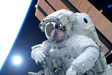 Astronaut In A Spacesuit, Against The Background Of The Earth, With The Sun Behind. Elements Of This Image Were Furnished By NASA.
