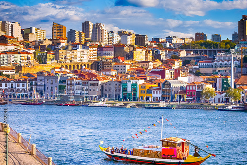 Foto  Port of City Porto in Portugal with Attraction Boat in Foreground