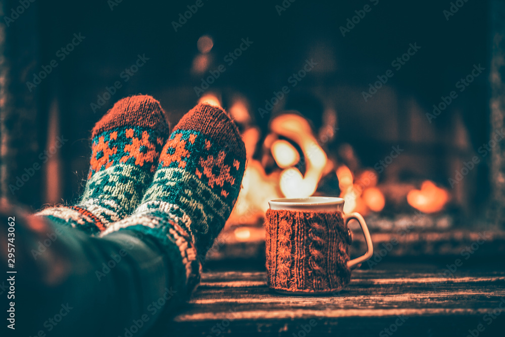Fototapeta Feet in woollen socks by the Christmas fireplace. Woman relaxes by warm fire with a cup of hot drink and warming up her feet in woollen socks. Close up on feet. Winter and Christmas holidays concept.