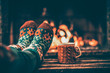 Leinwanddruck Bild - Feet in woollen socks by the Christmas fireplace. Woman relaxes by warm fire with a cup of hot drink and warming up her feet in woollen socks. Close up on feet. Winter and Christmas holidays concept.