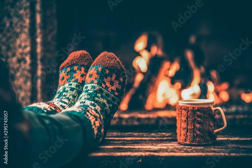 Fotomural  Feet in woollen socks by the Christmas fireplace