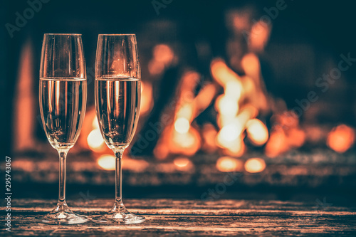 In de dag Alcohol Two glasses of sparkling champagne in front of warm fireplace. Cozy relaxed magical atmosphere in a chalet house by the fireside. Snug holiday concept. Beautiful background with shimmering wine.