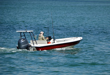 Red And White Fishing Skiff Powered By A Single Outboard Engine