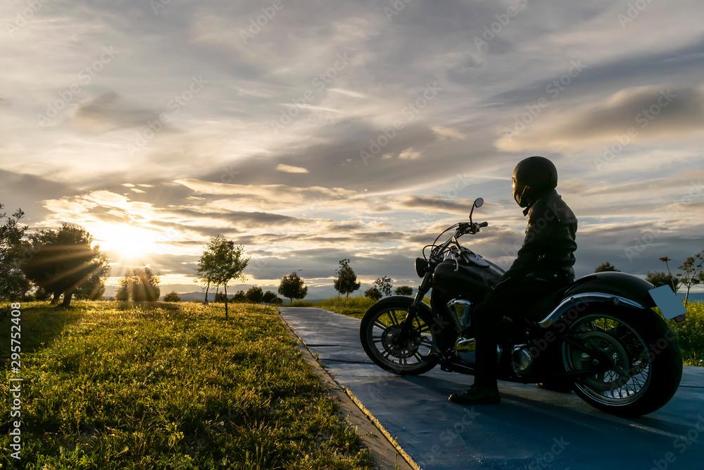 Fototapeta biker on the road on sunset