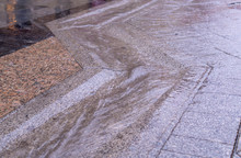 Urban Street Gutter With Water Flow On Tiled Sidewalk At Rainy Day. Background, Weather.