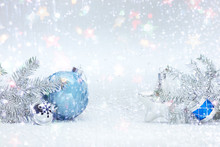 Festive Winter Holidays Composition On White Snow With Frosty Christmas Tree Branches, Decorative Blue Ball, Silver Glass Star And Drums Toy