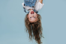 Beautiful Little Girl Hanging Upside Down On Blue Background