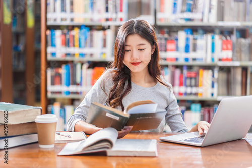 Foto Asian young Student in casual suit doing homework and using technology laptop in