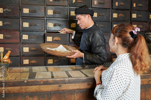 Foto  Traditional pharmacy worker putting dry shiitake mushrooms in basket when collec
