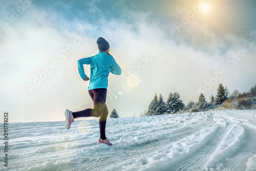 Running woman. Runner on the snow in winter sunny day. Female fi Fototapeta