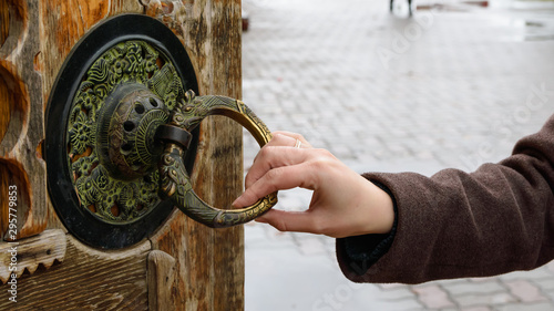 girl's hand holds an old round handle of a wooden door