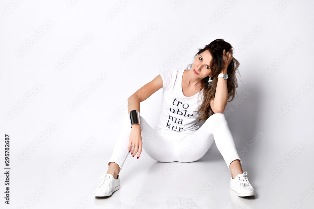 Fototapety, obrazy: Beautiful woman sitting in long white t-shirt and sneakers happy laughing full body on white background