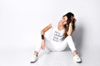 Beautiful woman sitting in long white t-shirt and sneakers happy laughing full body on white background