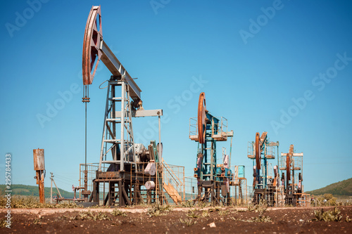 Fototapeta  Oil pump jack rocking with pipeline in the background