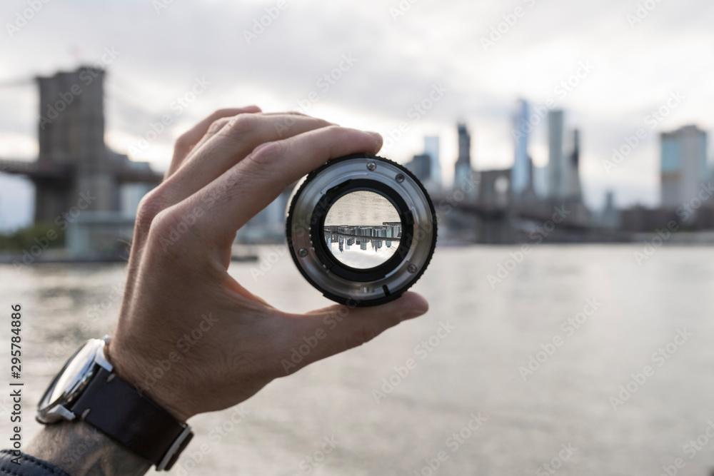 Fototapeta Hand holding a lens against New York City skyline