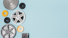 Different Type Of Film Reels Cases On Blue Background