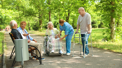 Group of elderly patients with nurse in park. Assisting seniors - 295786093
