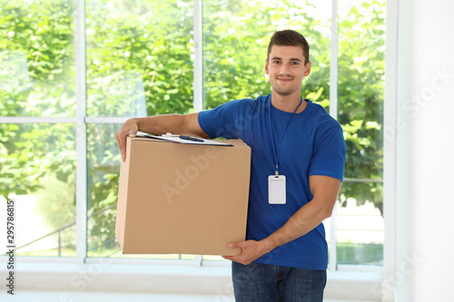 Happy young courier with cardboard box and clipboard near window indoors