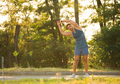 Young man doing exercise in park on sunny day