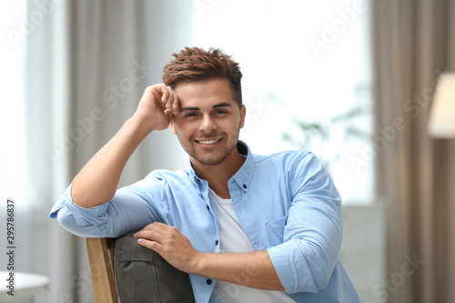 Fotografía  Portrait of handsome young man sitting on chair in room