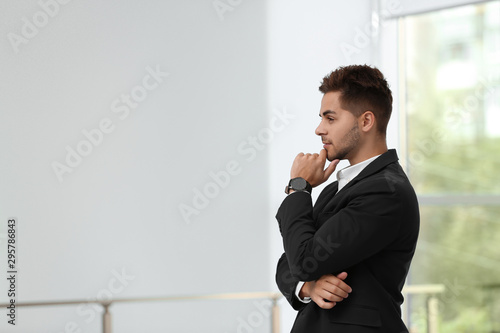 Portrait of handsome young man in elegant suit indoors. Space for text