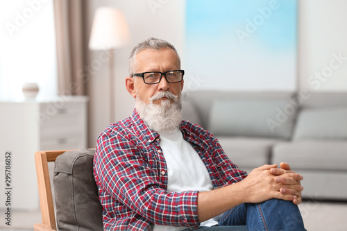 Fotografie, Obraz  Portrait of handsome mature man with glasses sitting on chair in room