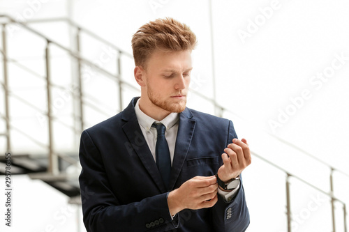 Portrait of handsome young man in elegant suit with wristwatch indoors