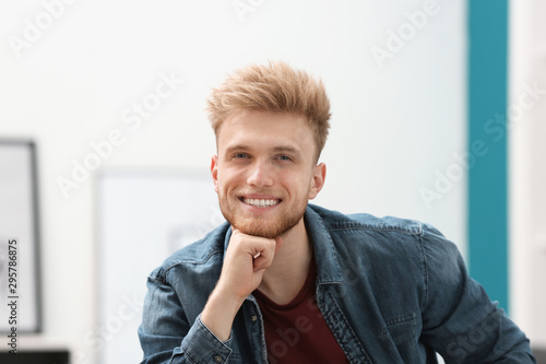 Portrait of handsome young man in room