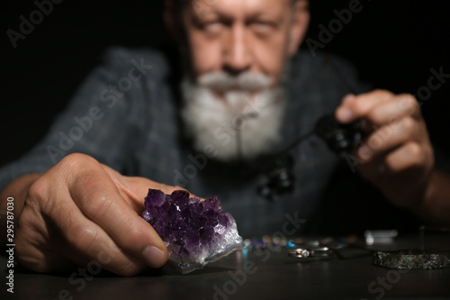 Male jeweler examining amethyst stone in workshop, closeup view