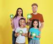 Leinwandbild Motiv Young family with recycling symbols on yellow background