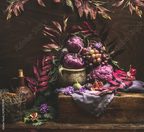 Fotografía  Still life with purple fruits and vegetables on wooden table with autumn leaves