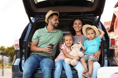 Fotografia, Obraz Happy family with suitcases near car in city street