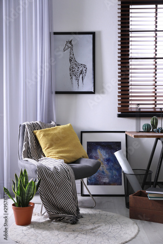 Comfortable armchair and table near window with horizontal blinds