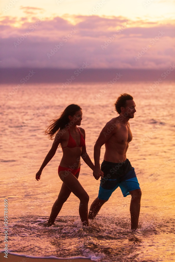 Fototapety, obrazy: Romantic beach walk silhouette of couple walking relaxing at sunset on tropical summer vacation destination. Travel holidays woman and man stroll outdoor.