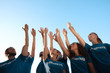 canvas print picture - Group of volunteers raising hands outdoors, low angle view