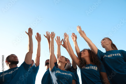 Group of volunteers raising hands outdoors, low angle view - 295788663