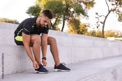Young man with wireless headphones listening to music on stairs. Space for text