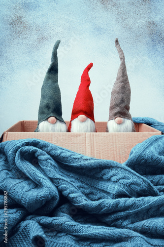 Three Christmas gnomes of different colors in open box, knitted blanket