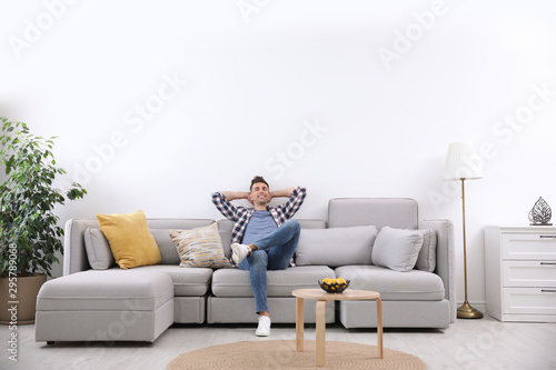 Fotografie, Obraz Young man relaxing on sofa under air conditioner at home