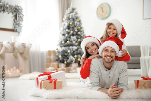 Obraz Portrait of happy family with Christmas gifts on floor at home - fototapety do salonu