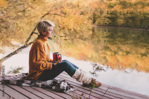 Poster Detente Woman sitting near lake with hot tea. Cozy fall.