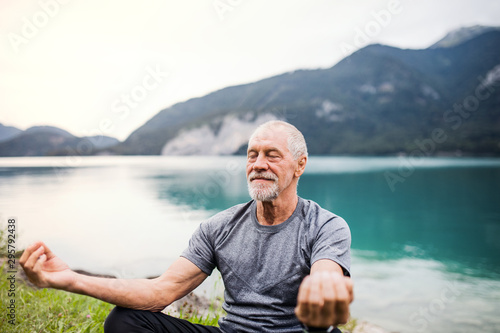 Pinturas sobre lienzo  A senior man pensioner sitting by lake in nature, doing yoga exercise
