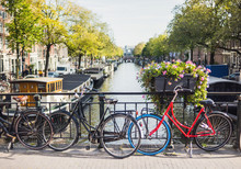 Charming Canal With Boat Houses And Bicycles In Amsterdam Old Town, Netherlands. Popular Travel Destination And Tourist Attraction. City Life Concept