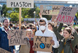 canvas print picture - People with placards and protective suit on global strike for climate change.