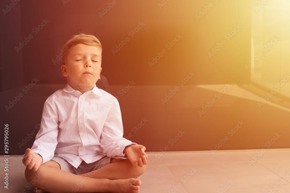Fototapeta Boy meditating with eyes closed.